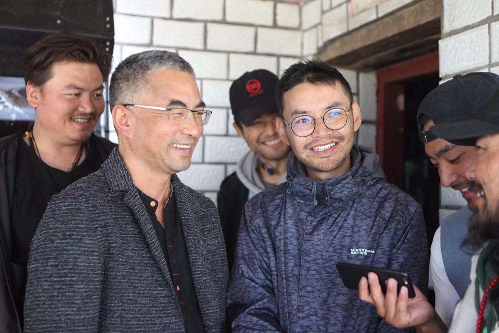 Pema Tseden (left, in square-framed glasses) and Lhapal Gya (right, in round glasses). Courtesy of Lhapal Gya