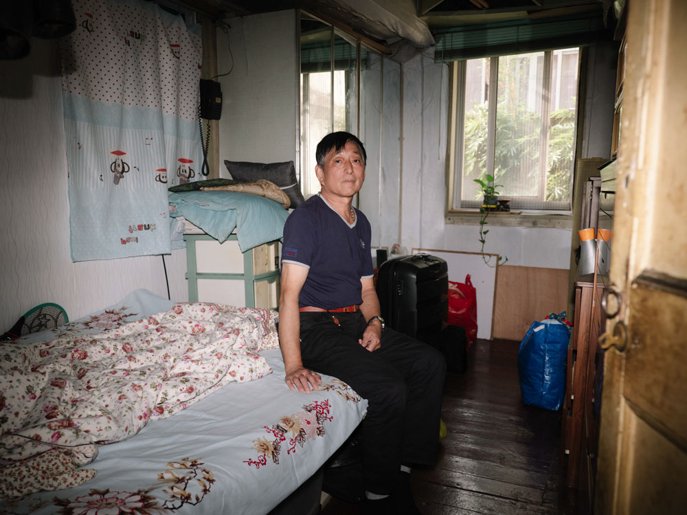Deng Deng sits on his bed in his old home in Yeguang Li, Shanghai, Oct. 17, 2020. Zhou Pinglang for Sixth Tone