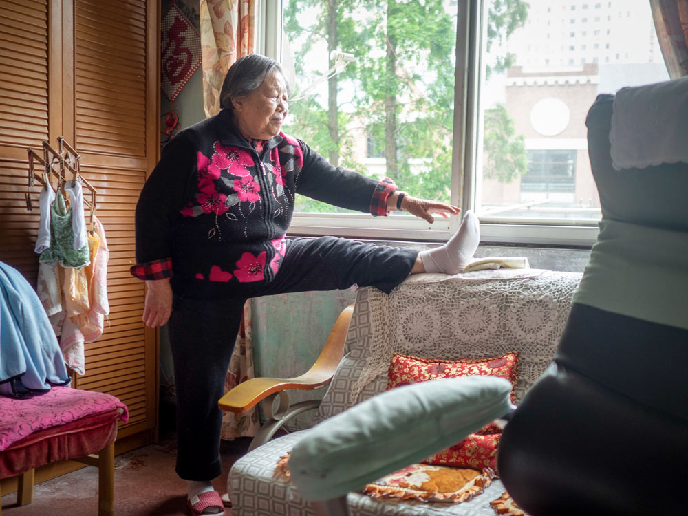 Yi Shijuan does some exercises at her home in Shanghai, April 27, 2021. Xu Haifeng for Sixth Tone