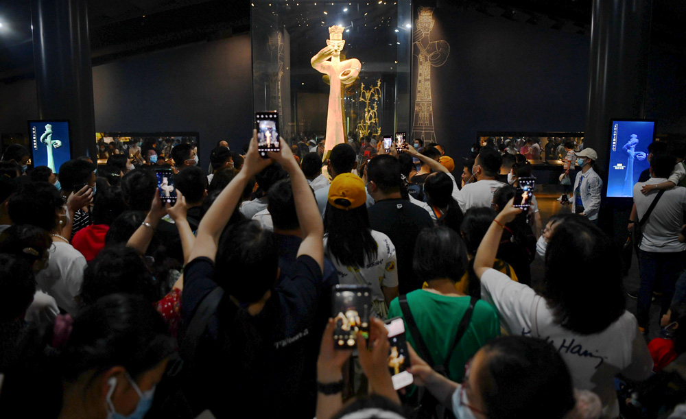 Tourists take photos of the Large Standing Figure at the Sanxingdui Museum, in Guanghan, Sichuan province, May 2021. The recent finds at Sanxingdui has renewed public interest in the project. Zhang Lang/CNS/People Visual