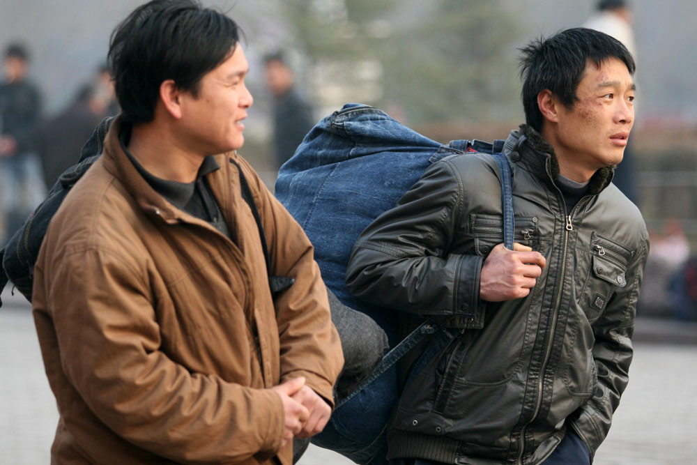Migrant workers make their way to the railway station after the Spring Festival holiday, in Xuchang, Henan province, Feb. 3, 2009. IC
