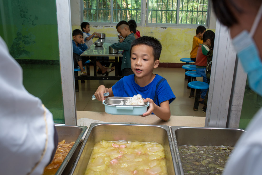A boy waits to be served at a rural primary school in Wangxia Township, Hainan province, Dec. 9, 2020. Yuan Chen/People Visual