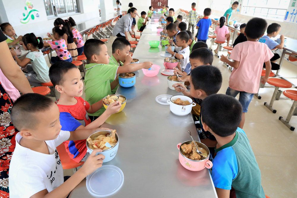Students enjoy a free lunch at a primary school in Rong'an County, Hubei province, 2019. Tan Kaixing/People Visual