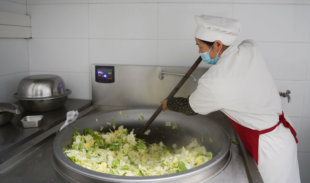 A cook fries vegetables for students at a primary school in Hefeng County, Hubei province, March 16, 2021. Yang Shunpi/People Visual