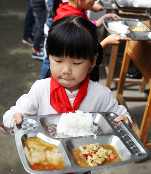 A girl walks carefully with her meal in Jingdezhen, Jiangxi province, Oct. 24, 2016. Xu Zheng/People Visual
