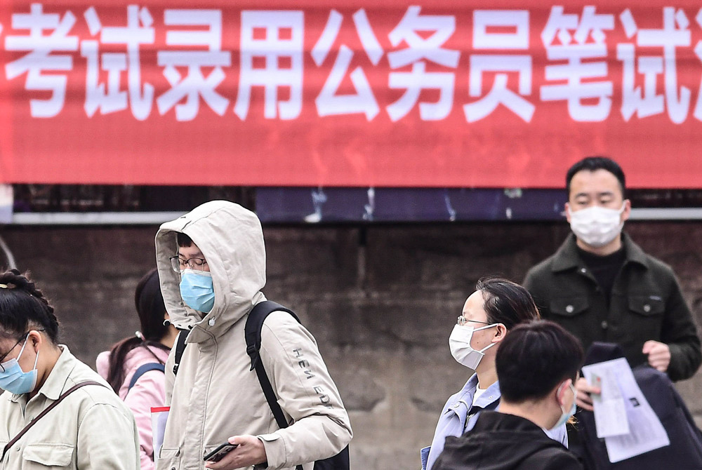 Test-takers wait to be let into a national civil service exam site in Shenyang, Liaoning province, March 27, 2021. People Visual