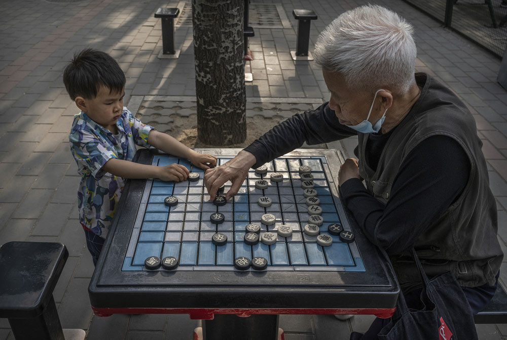 A man plays Chinese chess with his grandson at a local park in Beijing, May 12, 2021. Kevin Frayer/Getty Images/People Visual