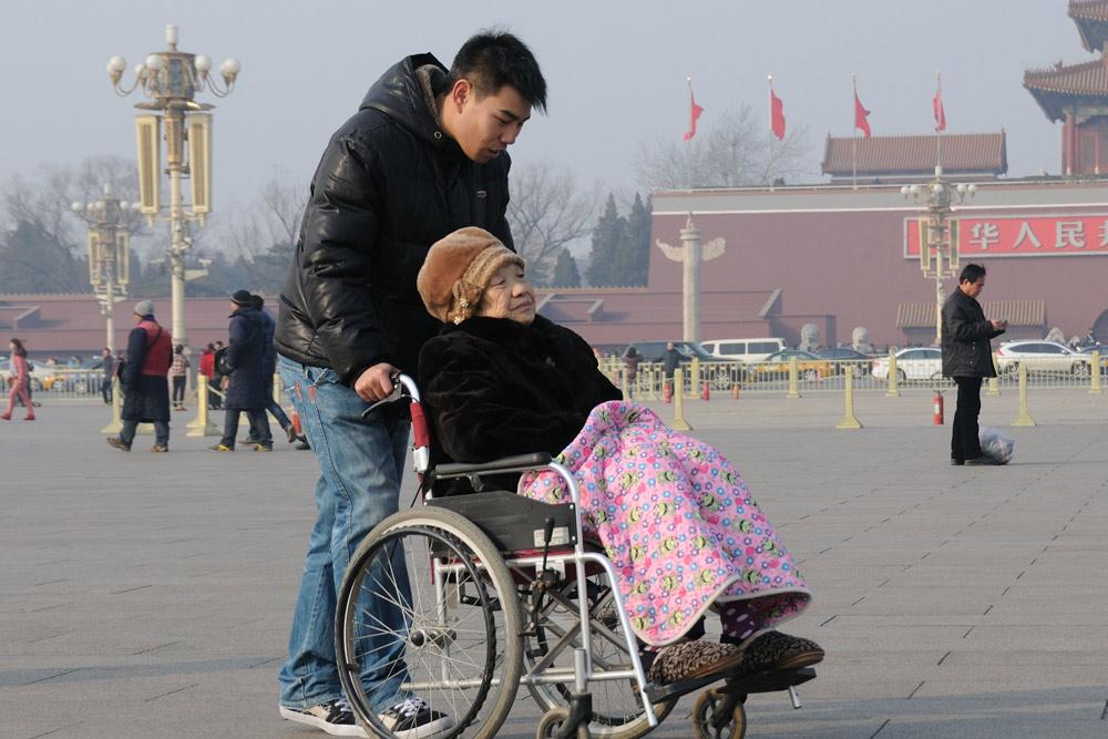 A man takes an elderly woman on a tour of Tiananmen Square in Beijing, Feb. 26, 2013. Jin Wen/People Visual
