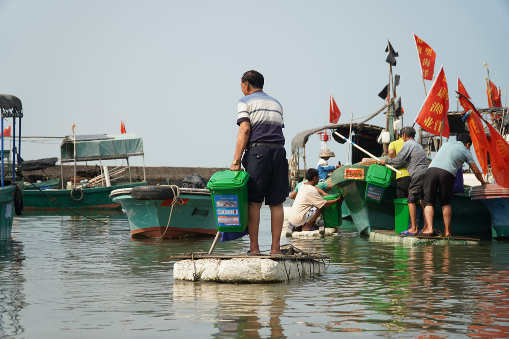 Fishermen load trash bins onto boats ahead of a trip to clean up fishery waste, Hainan province, March 15, 2021. Courtesy of Wang Songzi