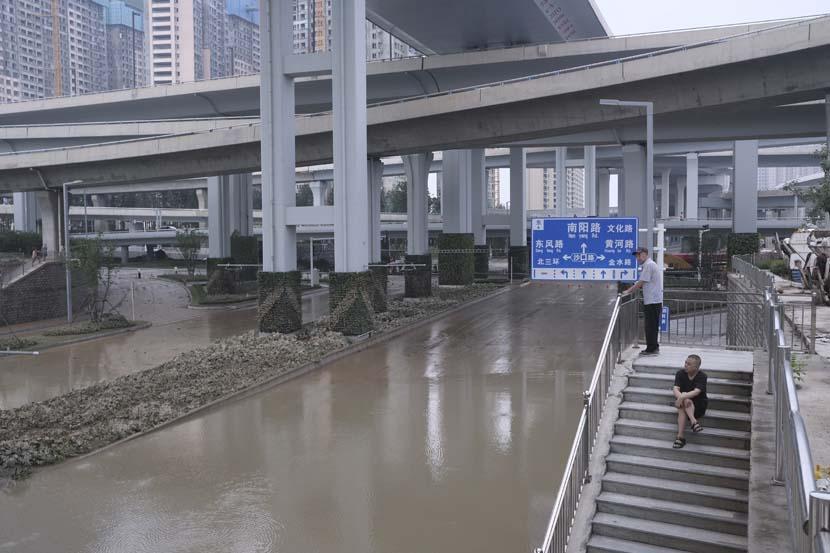 Two men look at a flooded street in Zhengzhou, Henan province, July 22, 2021. Wu Huiyuan/Sixth Tone