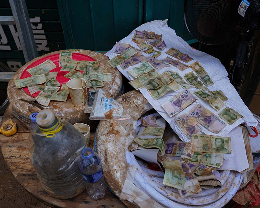 Paper money is left to dry in the sun after record rainfall in Mihe Town, Henan province, July 24, 2021. Xiao Yang for Sixth Tone