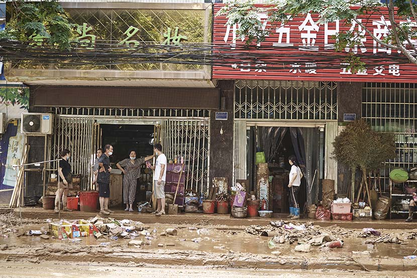 Shop owners chat outside a store in Mihe Town, July 24, 2021. Wu Huiyuan/Sixth Tone