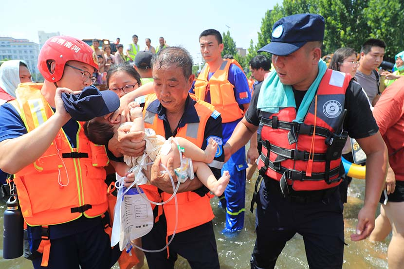 A sick baby is taken care of during the relocation of patients from the First Affiliated Hospital of Xinxiang in Weihui, Henan province, July 26, 2021. People Visual