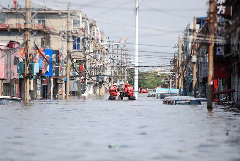 Rescue workers move local residents using an inflatable raft through a flooded street in Weihui, Henan province, July 27, 2021. People Visual