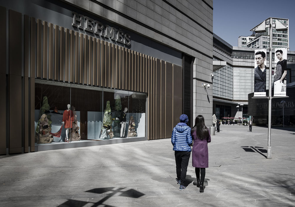 A couple walks past a Hermès store, in Beijing, March 14, 2017. Qilai Shen/Bloomberg/People Visual