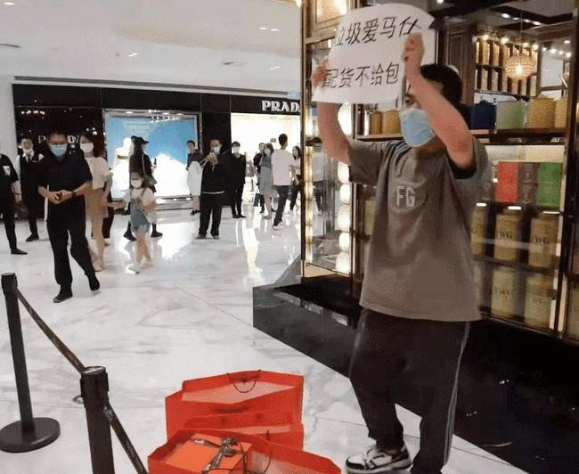 """A man holds a sign saying """"Rubbish Hermès — peihuo but no bag"""" outside a store in Beijing, July 2021. From """"DZ"""" on Xiaohongshu"""