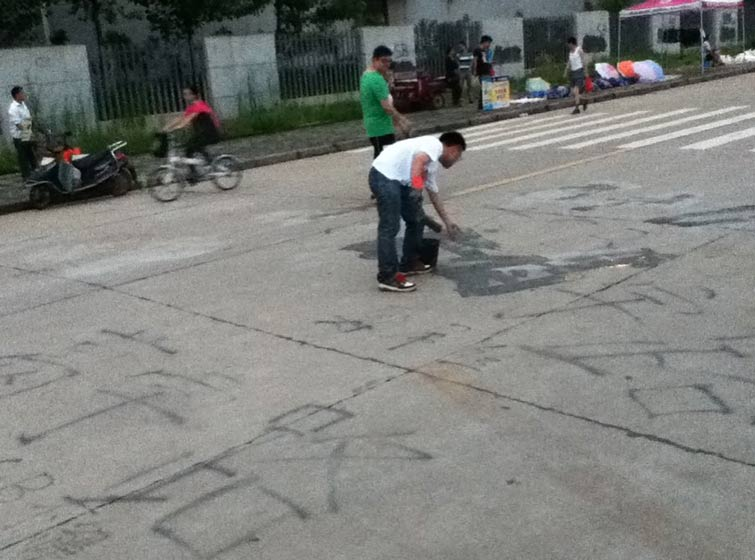 Ge Yulu covers up his graffiti using cement, in Wuhan, Hubei province. Courtesy of Ge Yulu