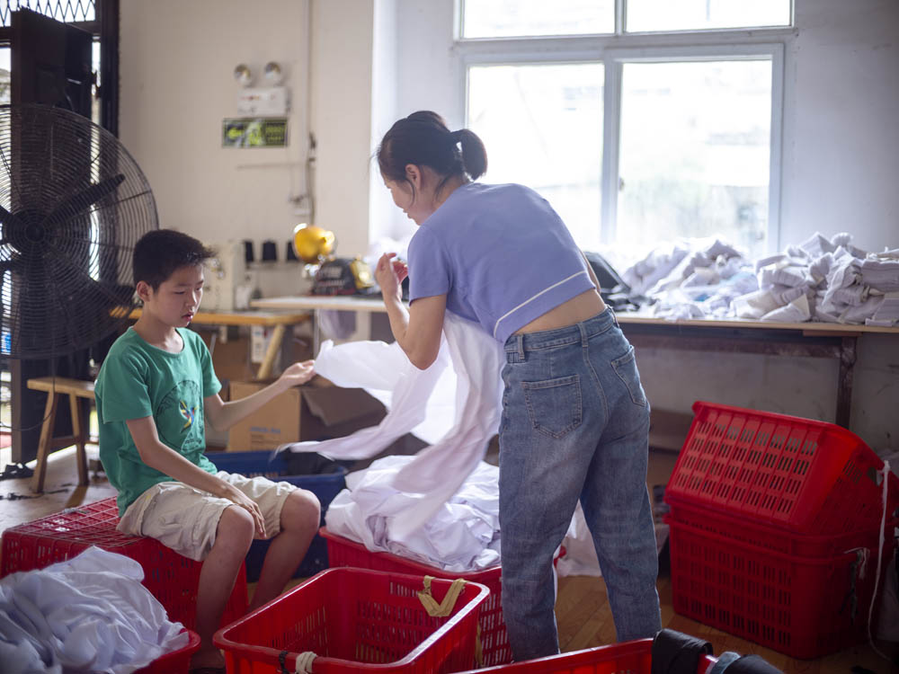 Xiaobao helps his mother with some basic tasks in the Plus Ten factory, June 2021. Courtesy of Lü Meng