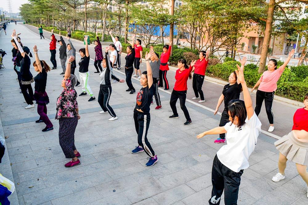 People dance on a riverbank in Dongguan, Guangdong province, 2019. Zhan Youbin/People Visual
