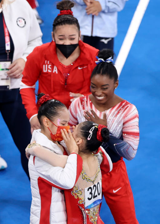 Tang Xijing and Guan Chenchen (No. 320) celebrate after the women's balance beam final as the United States' Simone Biles and Sunisa Lee look on, Aug. 3, 2021. Zheng Huansong/Xinhua