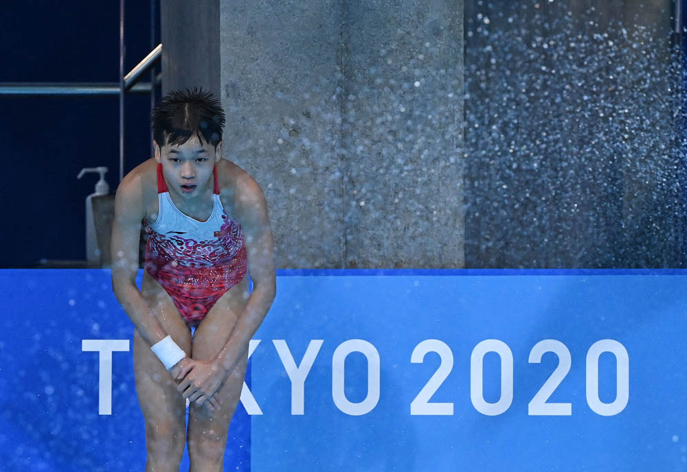 Quan Hongchan waits by the pool to see her final score during the women's 10-meter platform diving final, Aug. 5, 2021. Quan would go on to win the event. Attila Kisbenedek/AFP via People Visual