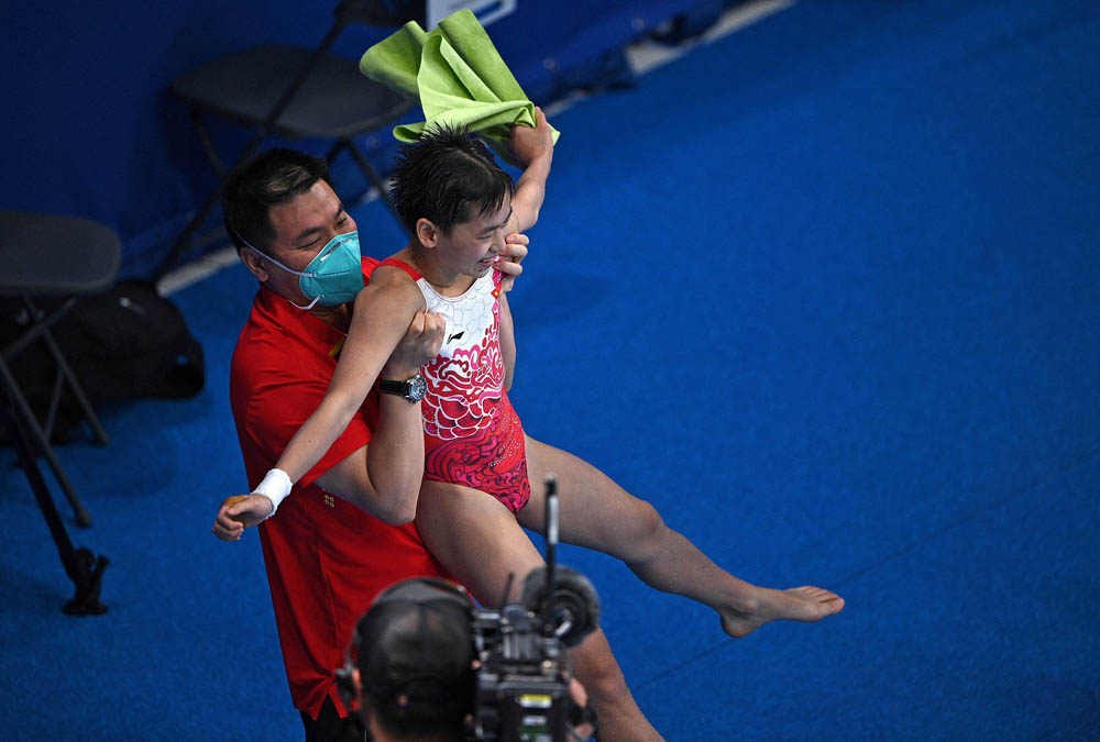 Quan Hongchan is lifted aloft by her coach after winning the women's 10-meter platform diving event, Aug. 5, 2021. Oli Scarff/AFP via People Visual