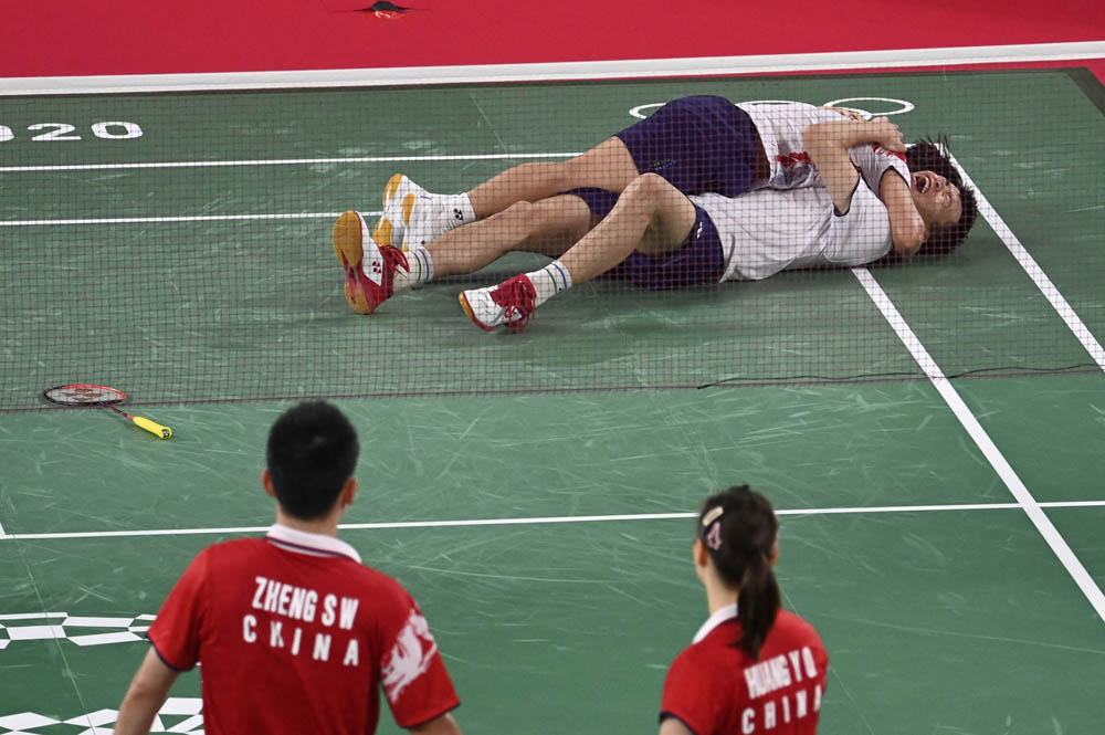 Huang Dongping (left) and Wang Yilü celebrate their win in the mixed doubles badminton final as Zheng Siwei (bottom left) and Huang Yaqiong look on, July 30, 2021. Alexander Nemenov/AFP via People Visual