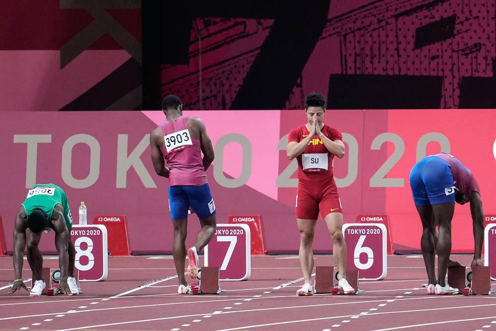 Sprinter Su Bingtian says a prayer before the men's 100-meter sprint final, Aug. 1, 2021. Wei Zheng/Sportsphoto/People Visual