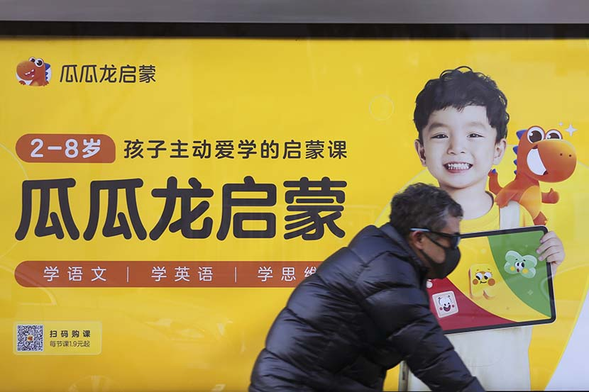 A man passes by an advertisement for Guagualong in Beijing, Dec. 21, 2021. People Visual