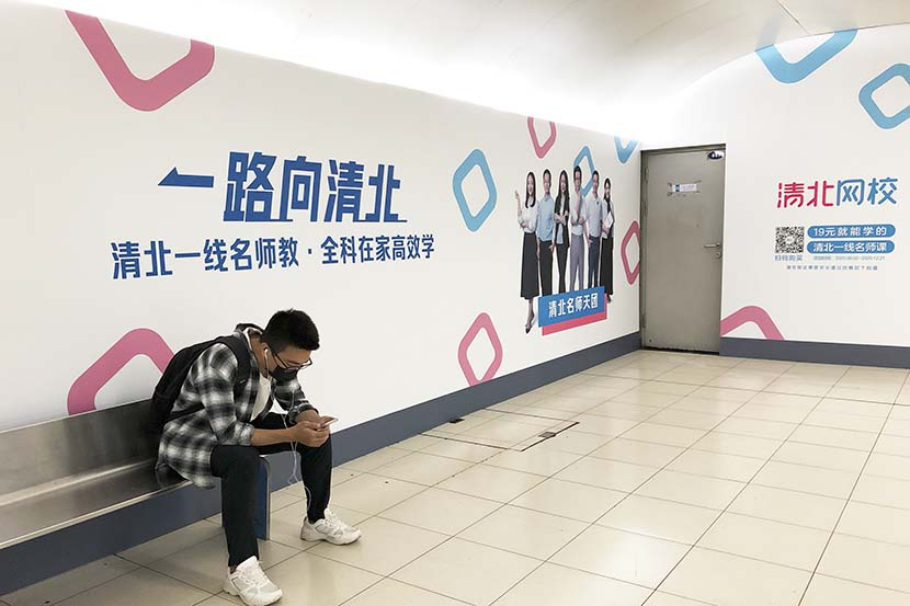 A man sits by an ad for Qingbei in Beijing, Sept. 7, 2021. People Visual