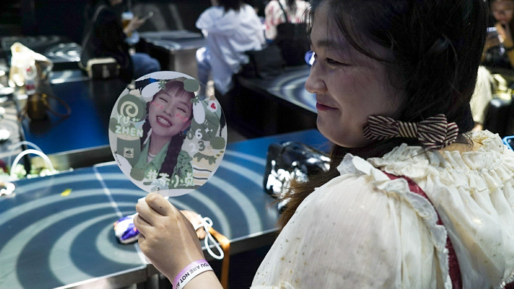 A fan of Yang Yuzhen holds a fan with a picture of Yang's face, Shanghai, June 22, 2021. Fu Beimeng/Sixth Tone