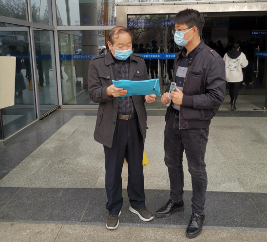 Lu (right) talks to his client outside of a hospital. Courtesy of Lu