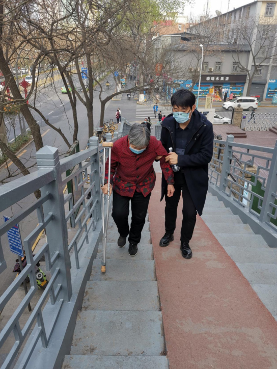 Lu escorts an elderly patient up the stairs. Courtesy of Lu