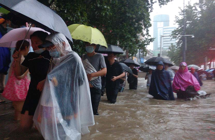 People walk through a flooded street outside a subway station in Zhengzhou, Henan province, July 20, 2021. IC