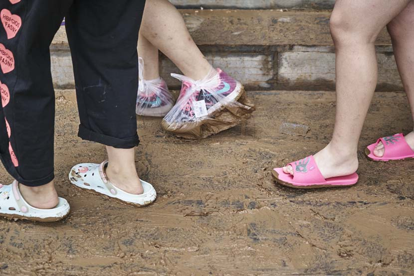 A woman wears plastic bags to cover her shoes in Mihe Town, Henan province, July 23, 2021. Wu Huiyuan/Sixth Tone
