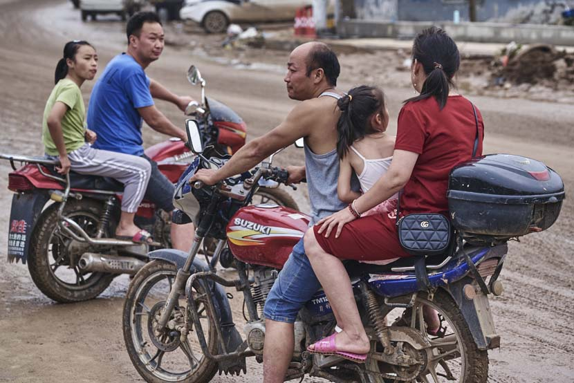 Villagers ride motorcycles on a muddy road in Mihe Town, Henan province, July 23, 2021. Wu Huiyuan/Sixth Tone