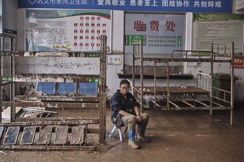 A woman sits in a flooded clinic in Mihe Town, Henan province, July 23, 2021. Wu Huiyuan/Sixth Tone