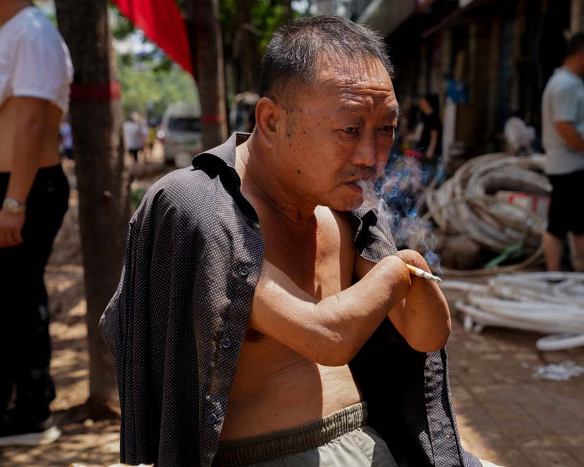 Zhang Tishan, owner of a hardware shop, smokes in Mihe Town, Henan province, July 24, 2021. Xiao Yang for Sixth Tone