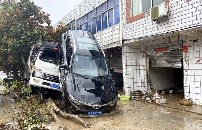 Two vehicles are damaged by flood waters in Suizhou, Hubei province, Aug. 13, 2021. People Visual