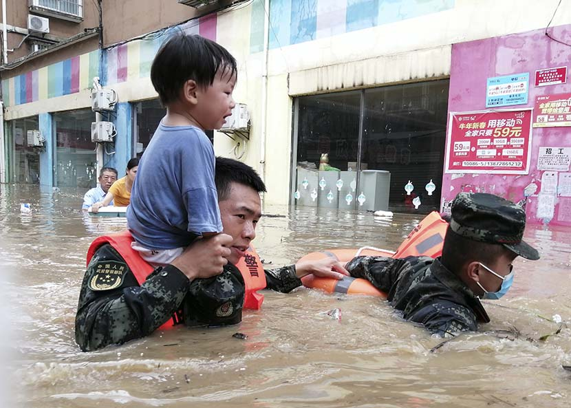Rescue workers carry a child through flood waters in Suizhou, Hubei province, Aug. 12, 2021. People Visual