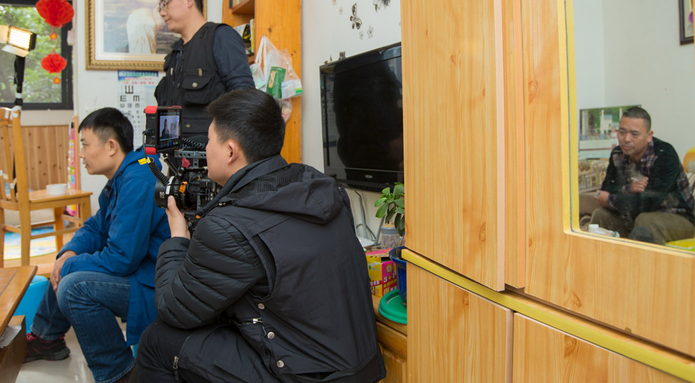 """Fan Jian (in blue) and a crew member shoot footage for the documentary """"After the Rain."""" Courtesy of Yu Zhuo"""