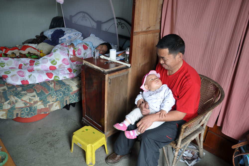 """A still from the 2011 documentary """"The Next Life"""" shows Zhu Junsheng holding his friend's newborn son. From Douban"""