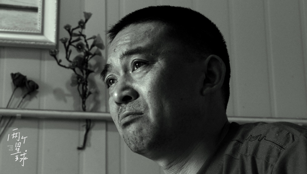 """A still shows the bereaved father Zhu Junsheng from the 2021 documentary """"After the Rain."""" From Douban"""