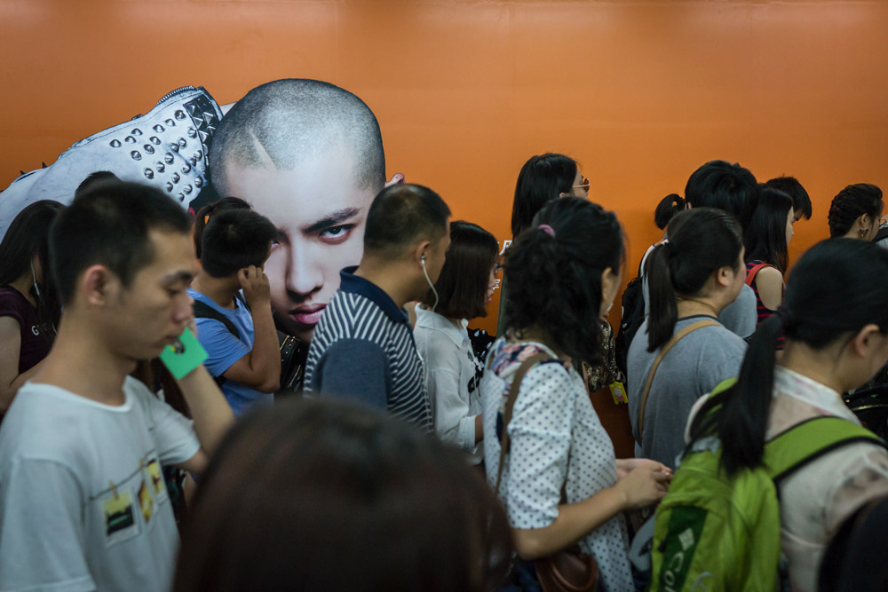 Passengers walk past an ad featuring Kris Wu at a subway station in Beijing, 2016. People Visual