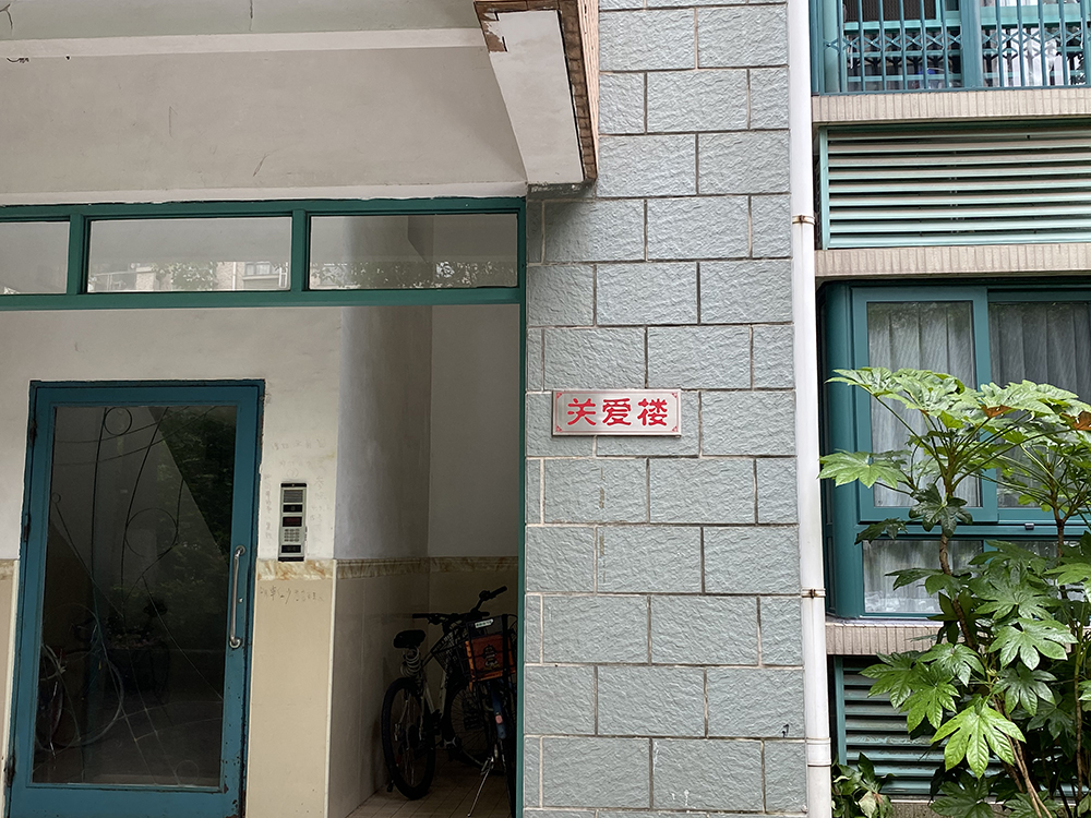 """The entrance to the building where the conflict took place, Shanghai, 2021. The sign reads """"care for the building."""" Chen Canjie for Sixth Tone"""