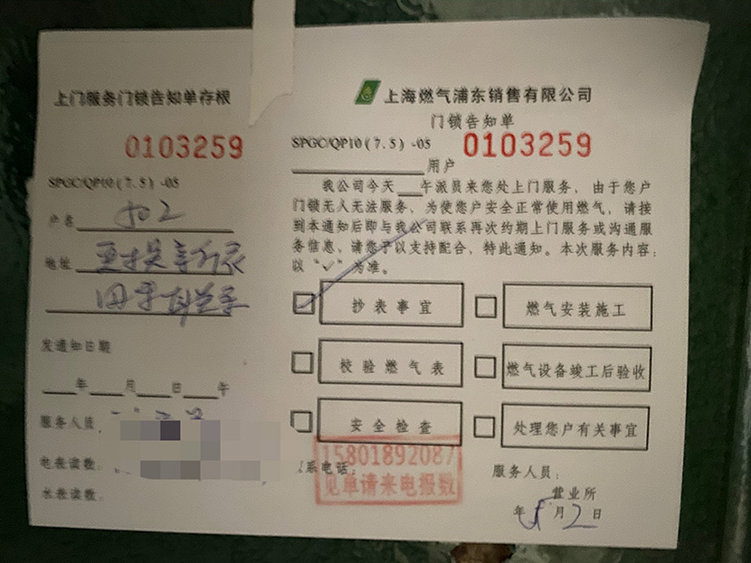 A notice regarding a replacement gas meter left on the door of Apartment 502, Shanghai, 2021. Chen Canjie for Sixth Tone