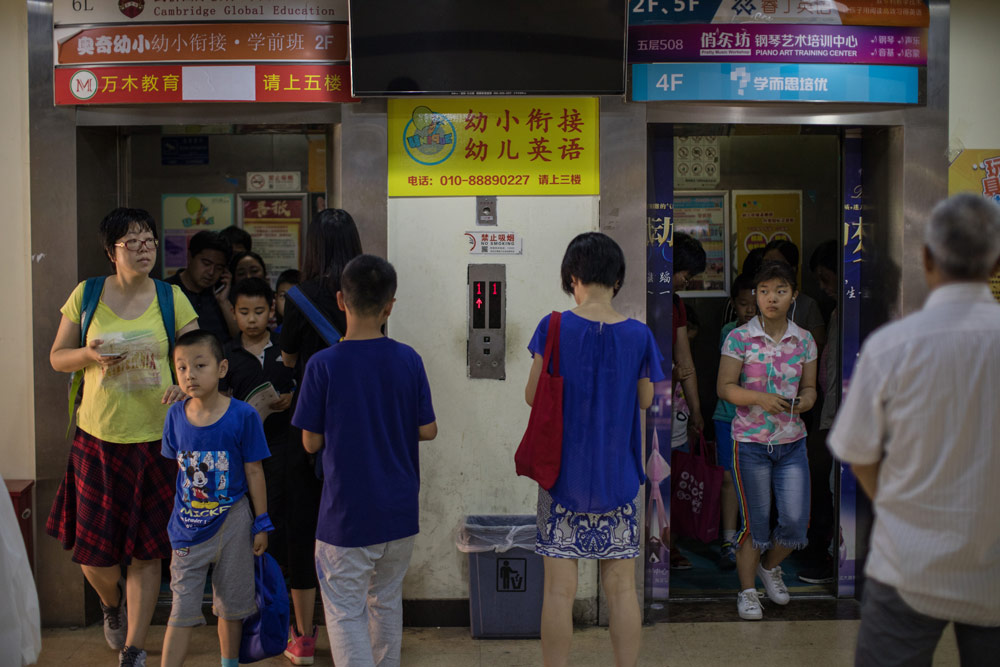 Students exit an elevator at a building housing multiple tutoring companies in Beijing, May 27, 2018. Li Jianguo/People Visual