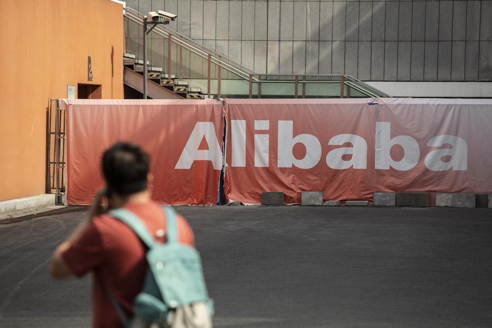 A man walks past a sign at Alibaba's headquarters in Hangzhou, Zhejiang province, May 8, 2021. Qilai Shen/Bloomberg via People Visual