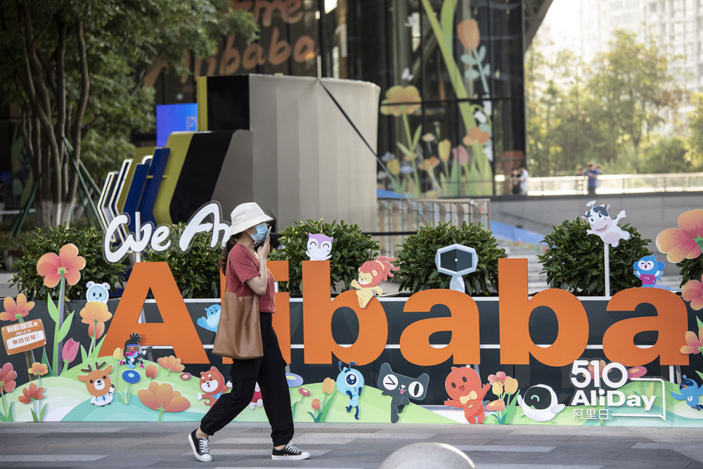 A woman walks past a sign at Alibaba's headquarters in Hangzhou, Zhejiang province, May 8, 2021. Qilai Shen/Bloomberg via People Visual