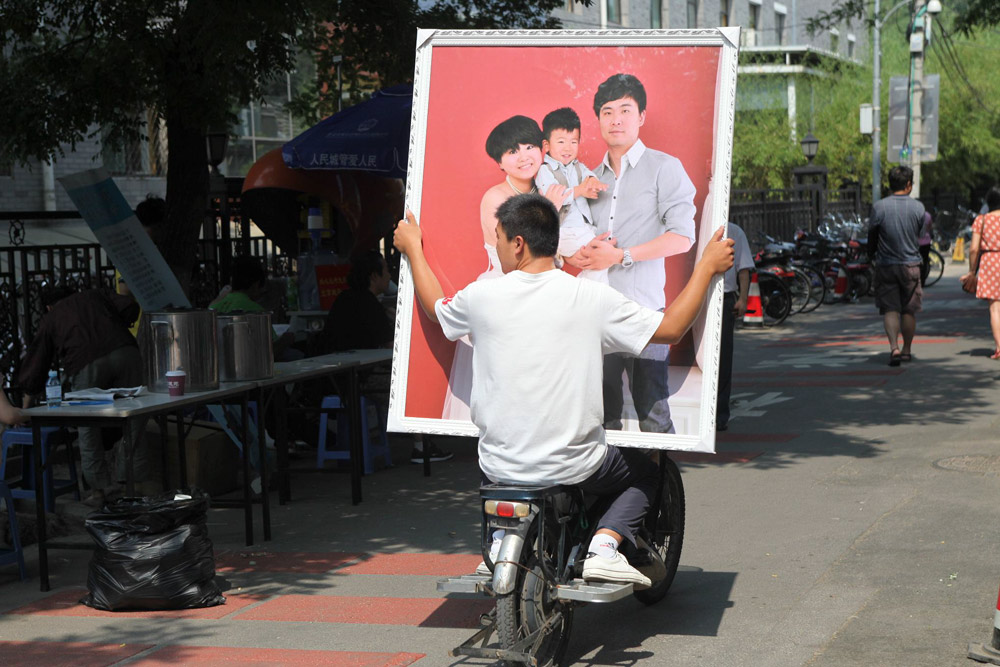 A man helps transport a large family photo in Beijing, 2012. Zhang Jusheng/People Visual